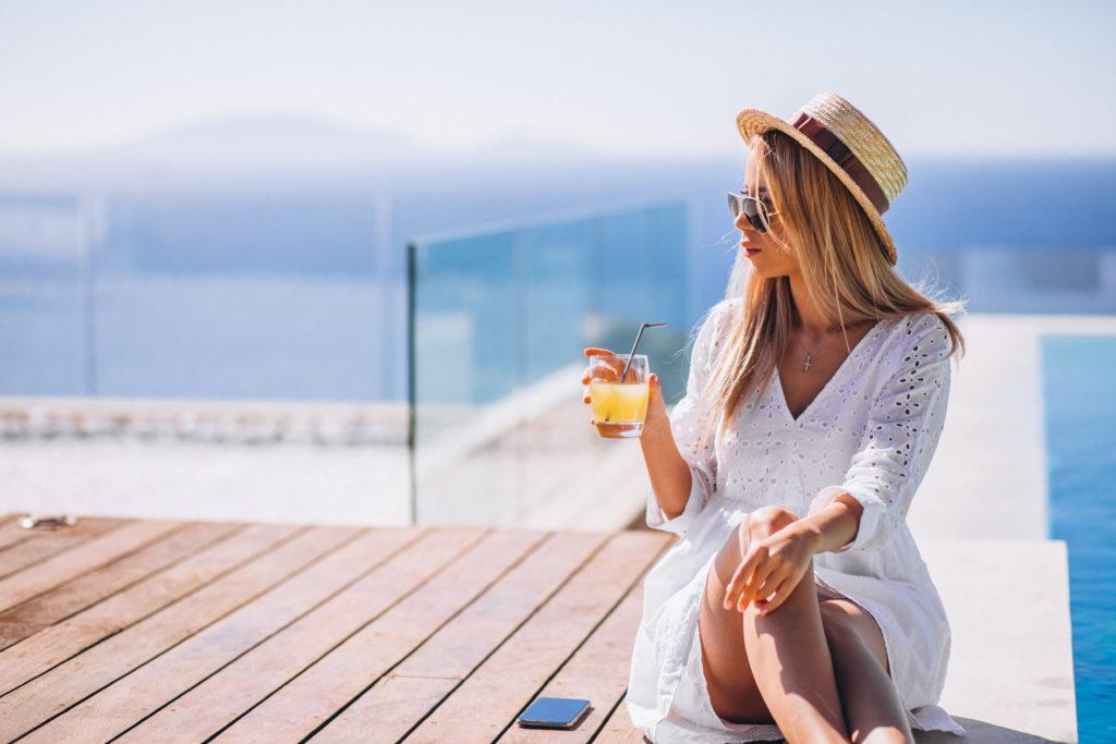 Young woman drinking juice bu the pool