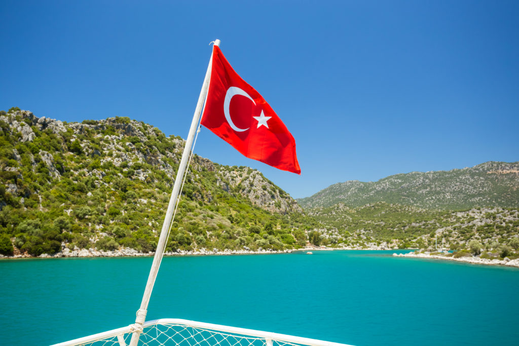Flag of Turkey on the background of the coast and the sea bay