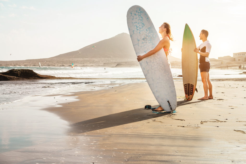 Surfers couple waiting for the high waves on beach - Sporty people with surf boards at sunset - Extreme sport and vacation concept - Focus on female face