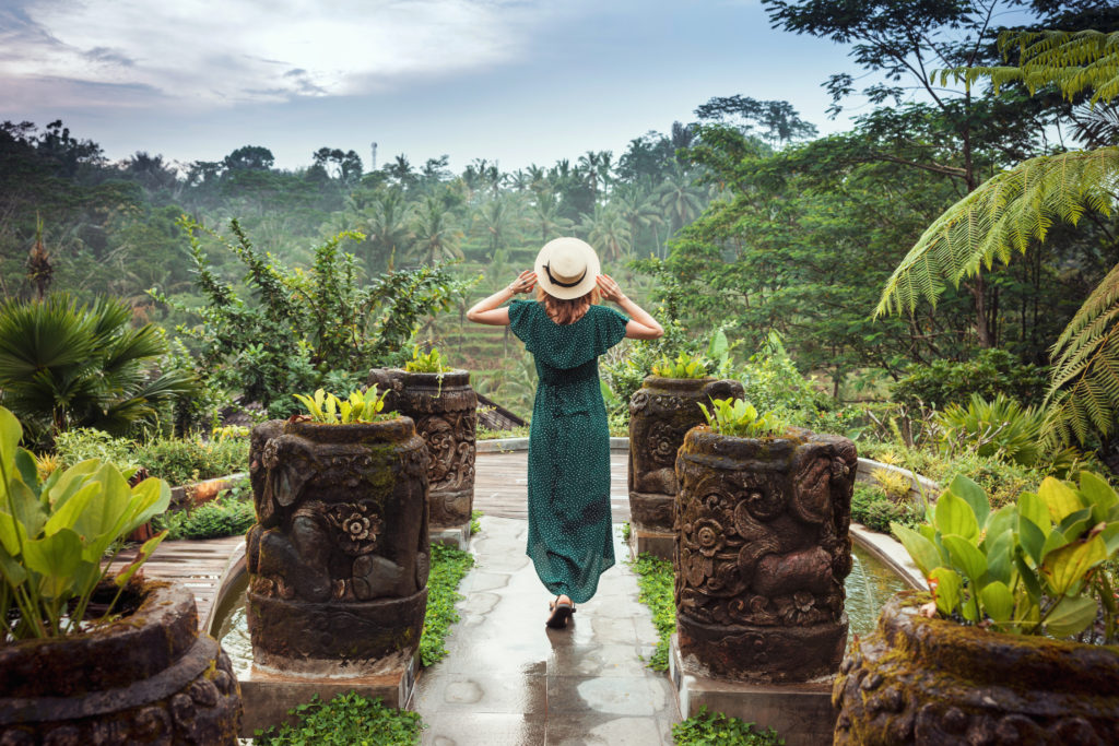 A young woman in a long dress of emerald color and wearing a hat is standing with her back against the background of a green tropical jungle, Ubud, Bali. Girl in a romantic image among the plants