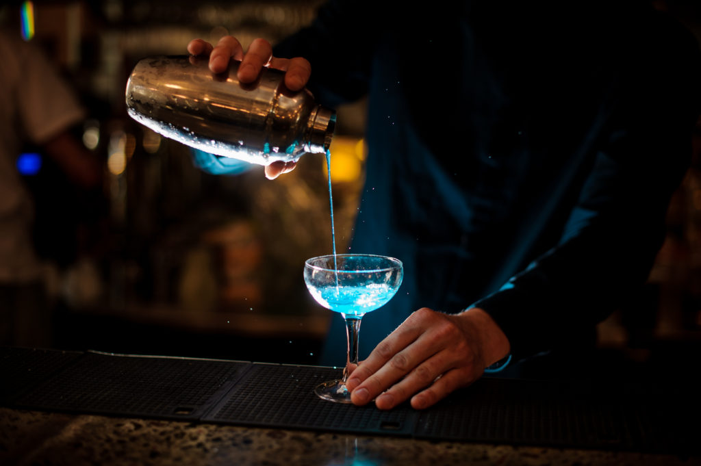 barman in a blue shirt pours from a shaker into a glass of alcohol cocktail Blue Lagoon on a dark background in the bar