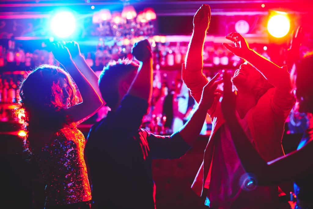 Group of dance lovers enjoying disco in nightclub