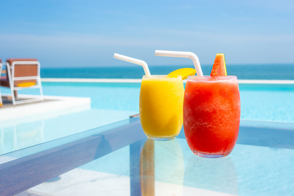 watermelon smoothie and mango smoothie on table with swimming pool and sea beach background