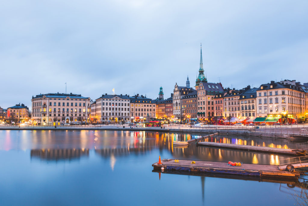 View of Stockholm old town at dusk. Long exposure shot, with water on foreground and blurred clouds on the sky. Typical scandinavian architecture and colors. Travel and tourism concept.