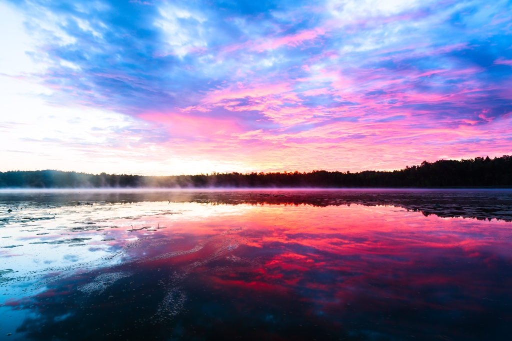 Bright colorful foggy sunset on the lake with clouds and reflections in Finland. Nature amazing sunrise background