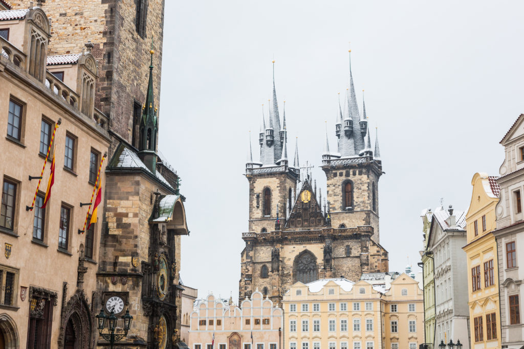 View of Prague main buildings with snow covered rooftops. On the left there is the tower with the famous astronomical watch and on background the Cathedral. Winter and travel concepts.