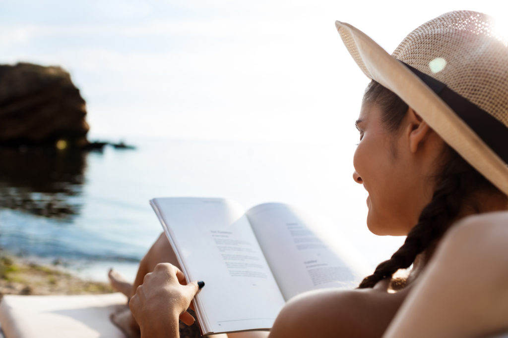 Beautiful brunette girl in hat smiling, reading book, lying at sea beach. Copy space.