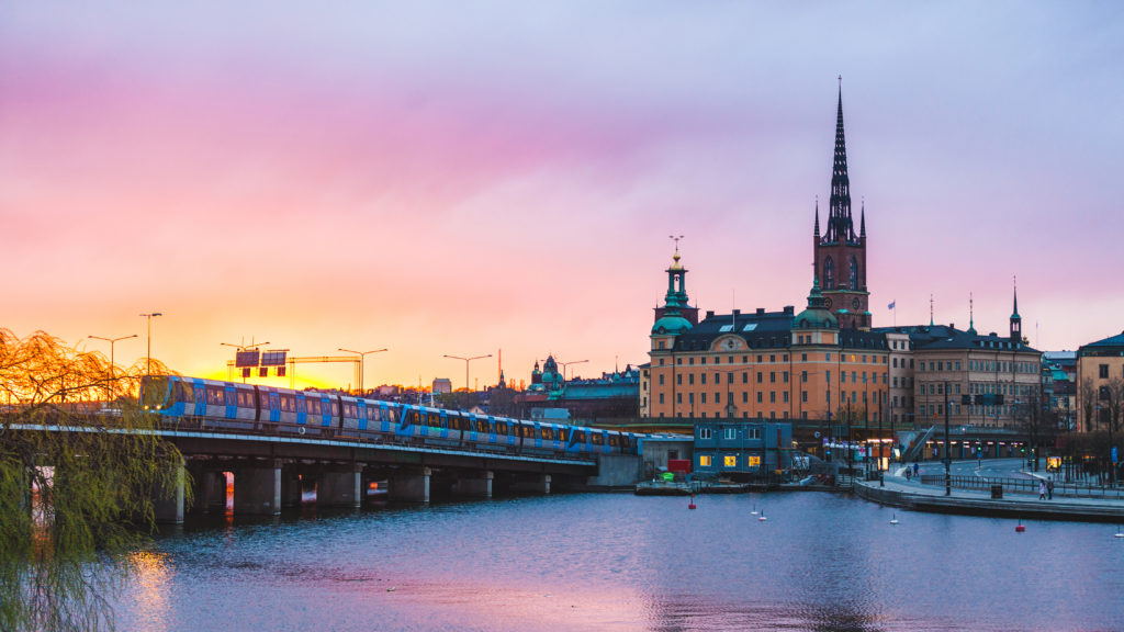 View of Stockholm old town and metro train at sunset. Typical scandinavian architecture and colors with pink and orange clouds. Travel and tourism concept in the capital city of Sweden.