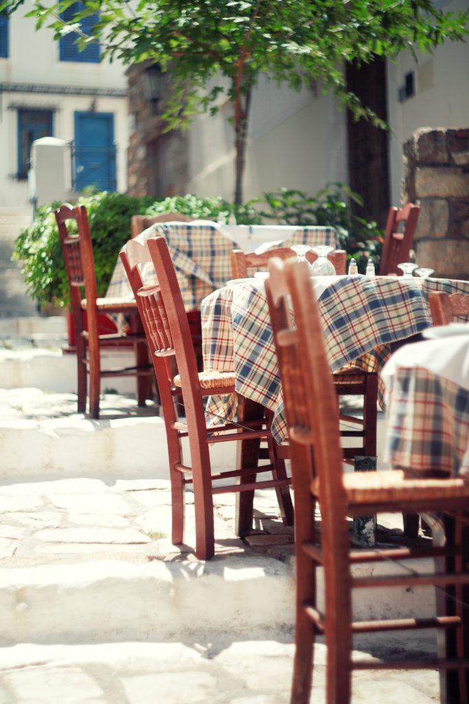 Cafe tables and chairs outside, Athens, Greece.Toned vintage photo.