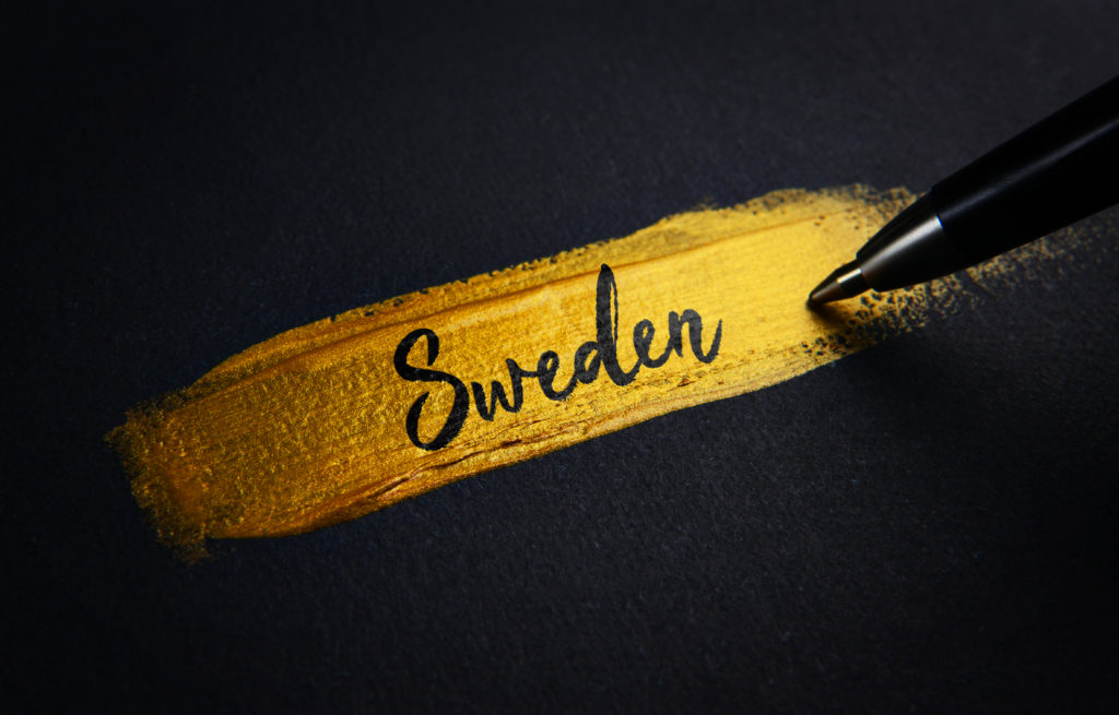 Sweden Handwriting Text on Golden Paint Brush Stroke