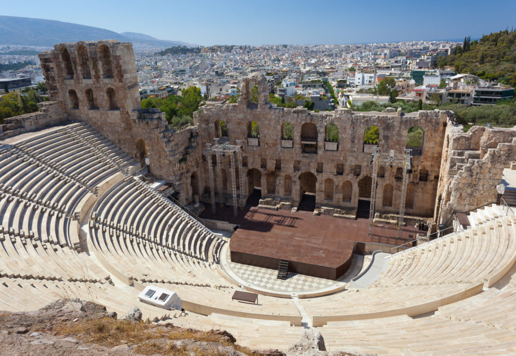 The Odeon of Herodes Atticus with the city of athens is in the background.