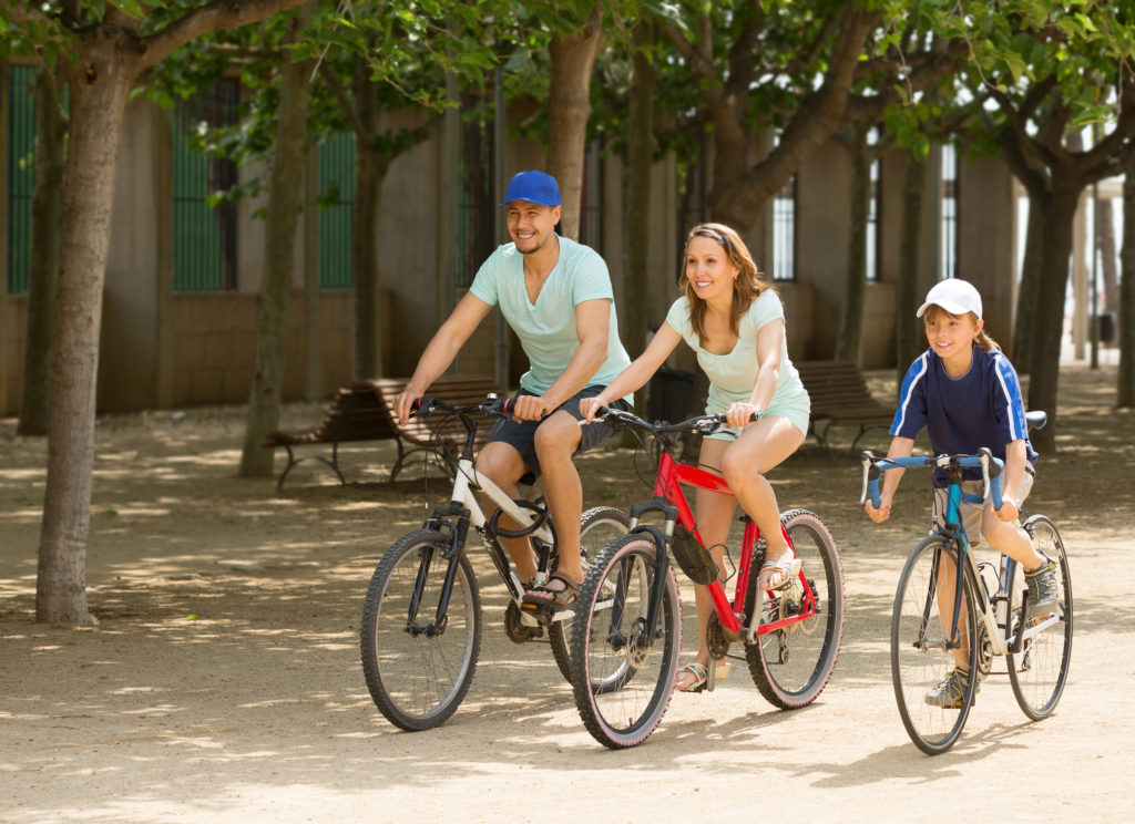 Happy family of three cycling on street road in summer day