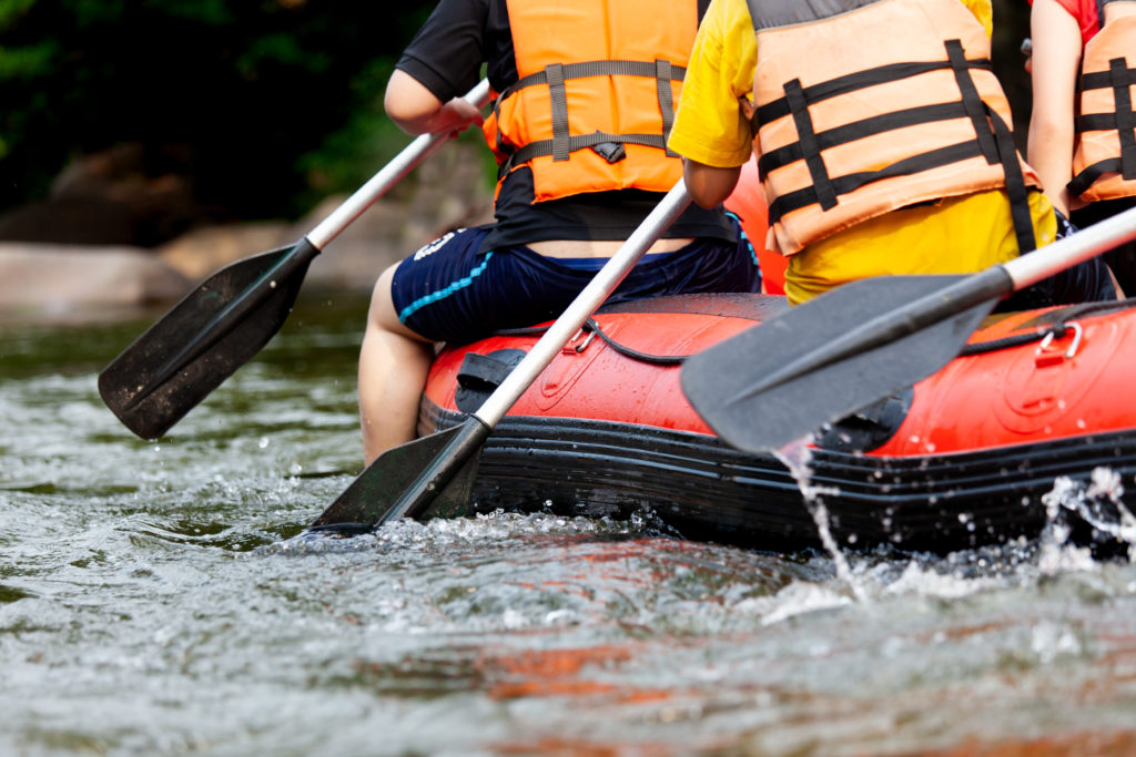 Young person rafting on the river, extreme and fun sport at tourist attraction natural park