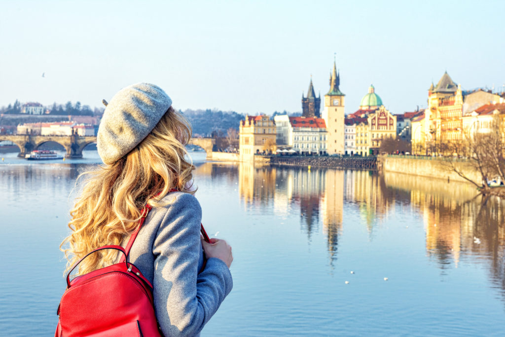 Tourist girl dicovering Prague, Czeh Republic. Charles bridge view on background