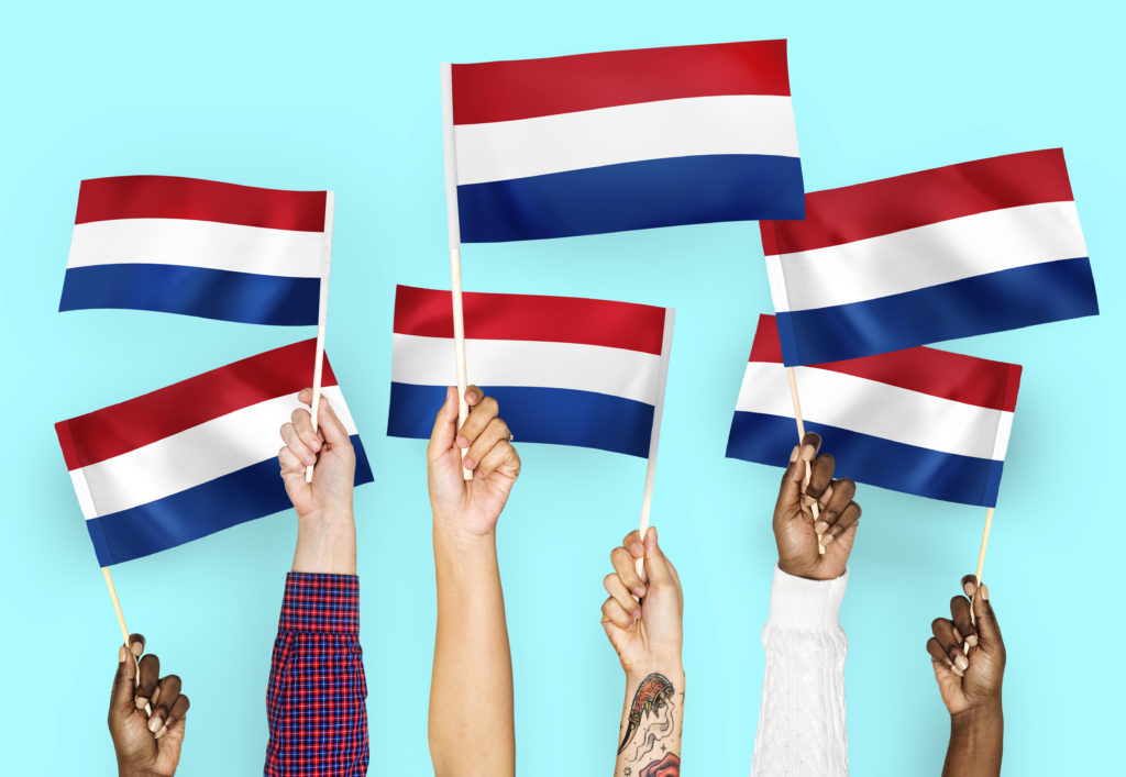 Hands waving flags of the Netherlands