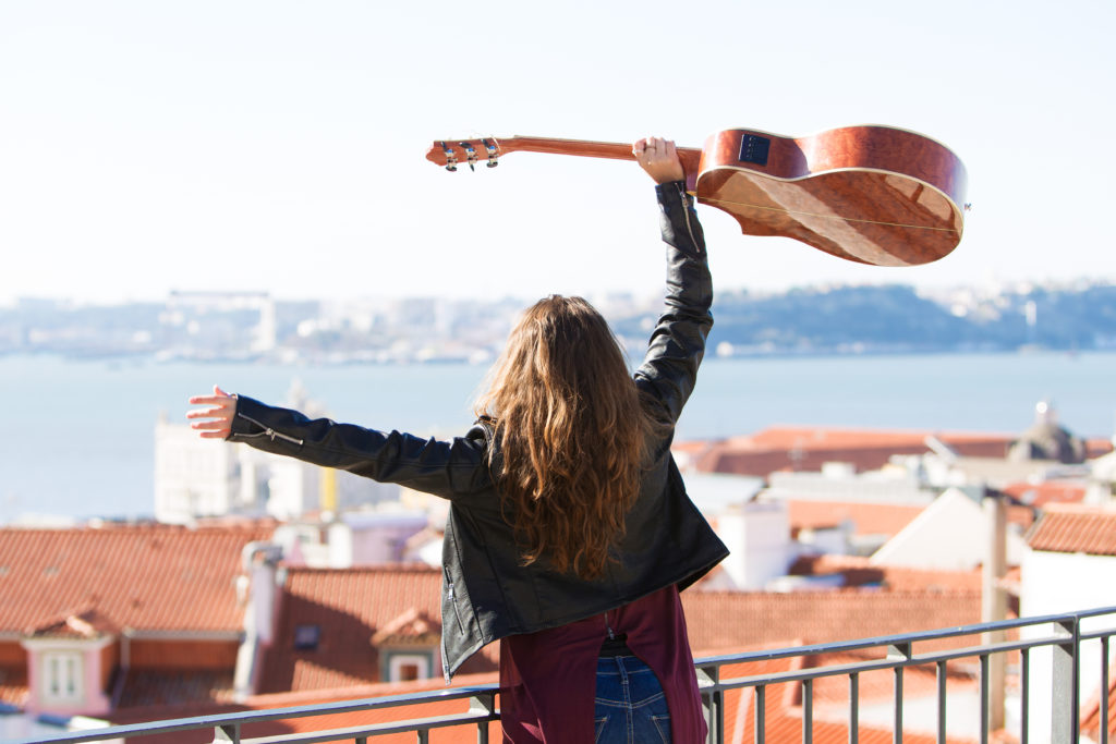 Closeup of cheerful young beautiful woman standing on rooftop in city and holding guitar above head. Back view.