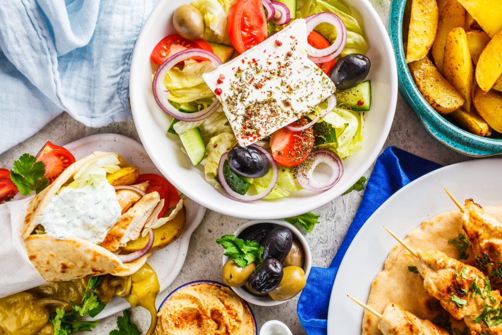 Flat lay of Greek food: greek salad, chicken souvlaki, gyro and baked potatoes on a gray background, top view. Traditional greek cuisine concept.