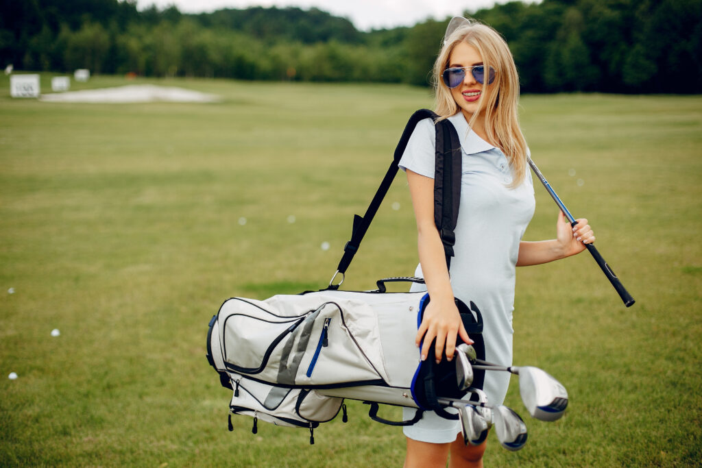Girl in a golf course. Blonde in a sport clothes. Woman playing golf