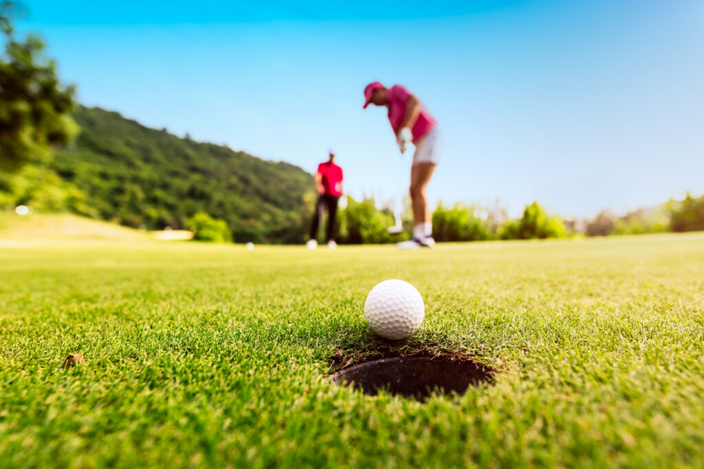 golfer-focus-putting-golf-ball-into-hole-during-sunset-healthy-lifestyle-concept